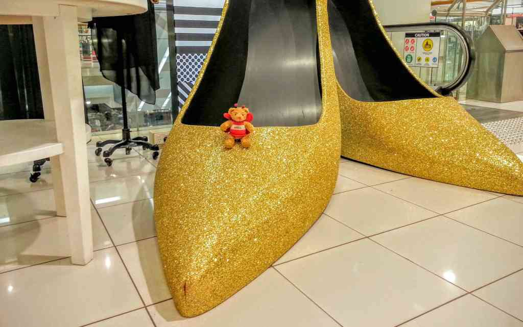 BeeBear tries on a pair of golden dancing shoes. They are a bit too big.