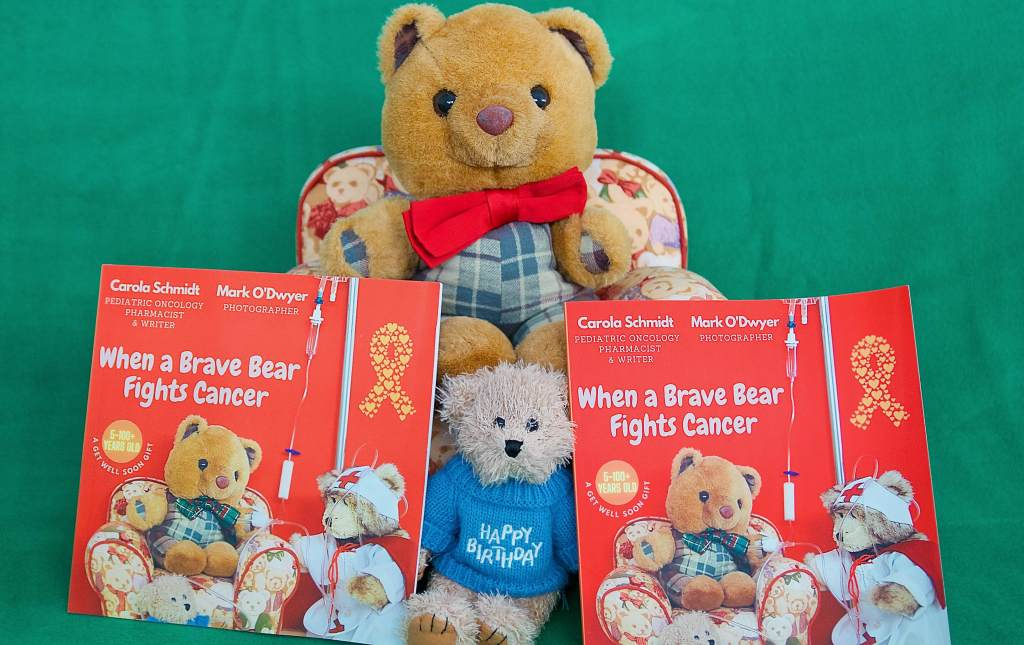Scotland the Brave, who stars in When A Brave Bear Fights Cancer, shows the book so you can see what it looks like. The little teddy in the blue jumper is Little Teddy. He is also in the book